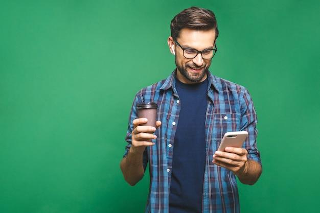 Ritratto del giovane felice che parla sul telefono e che beve tè. isolato su sfondo verde