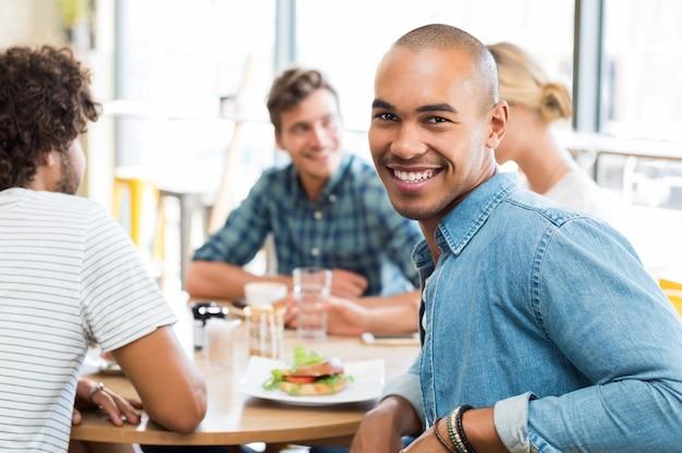 Ritratto di giovane uomo felice con i suoi amici che mangiano alla caffetteria in parete
