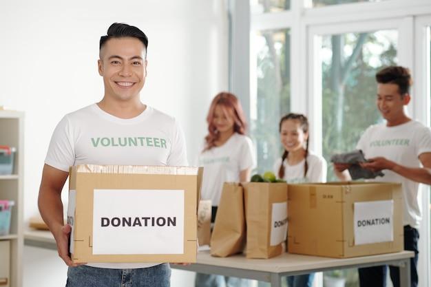 Ritratto di un giovane uomo felice che lavora in una fondazione di beneficenza e imballa scatole per le donazioni per la banca del cibo