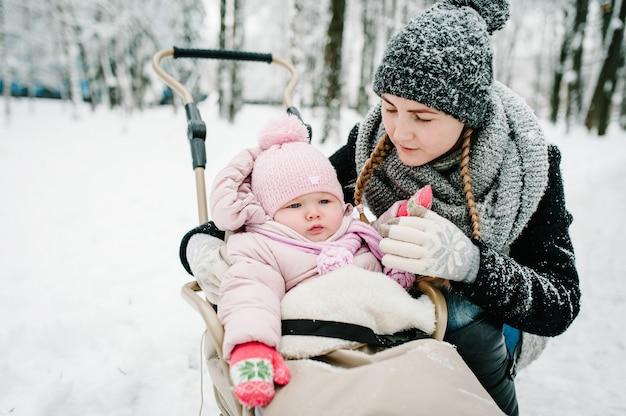 Ritratto felice giovane madre con la figlia in inverno. famiglia felice che cammina nel parco.