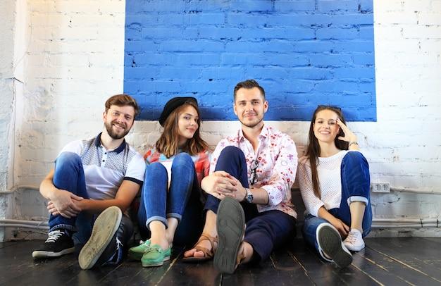 Ritratto di giovani felici in una riunione che guarda l'obbiettivo e sorridente. giovani designer che lavorano insieme a un progetto creativo.