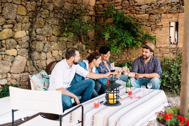 Ritratto dei giovani felici che si siedono insieme e che ridono mentre godendo ad una festa con vino sulla tavola.