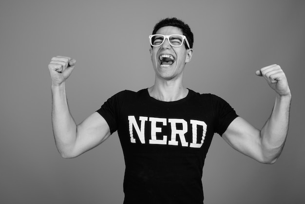 Ritratto di felice giovane nerd persiano che riceve buone notizie