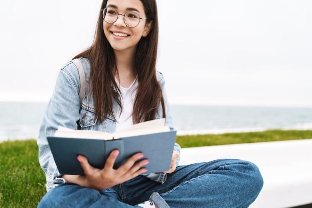 Ritratto di felice giovane ragazza adolescente che indossa occhiali sorridendo e leggendo un libro mentre è seduto sull'erba verde in riva al mare