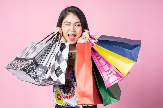 Ritratto di giovane donna felice che trasporta molti sacchetti colorati