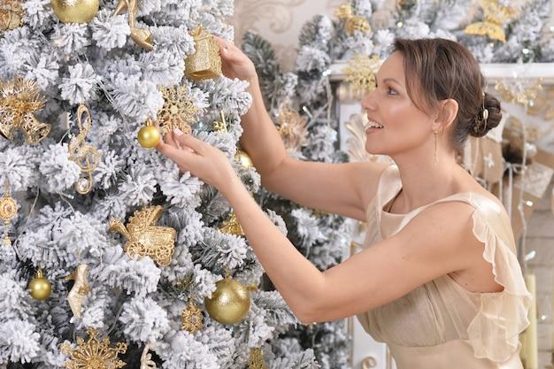 Ritratto di giovane donna felice che decora l'albero di natale