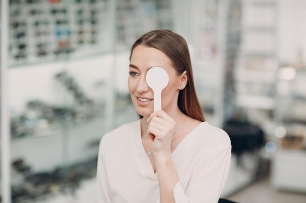 Ritratto di giovane donna felice durante l'esame della vista presso l'ottico optometrista.