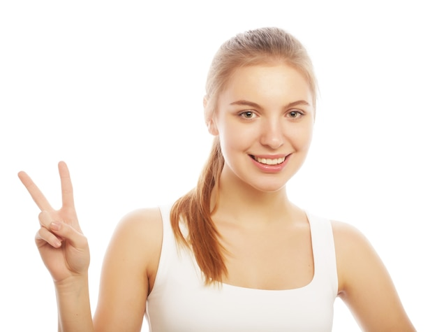 Ritratto di giovane donna felice che dà segno di pace isolato su bianco