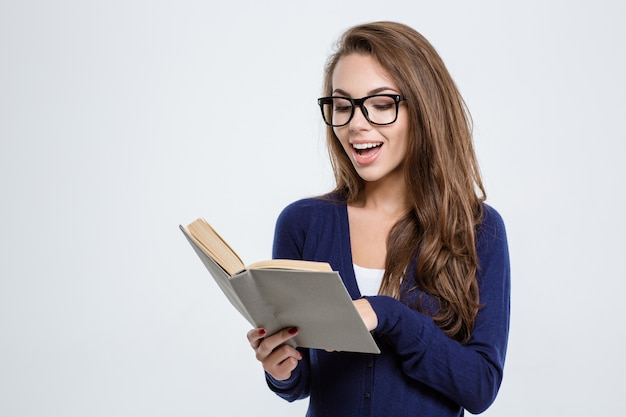 Ritratto di una giovane donna felice con gli occhiali che legge un libro isolato su uno sfondo bianco