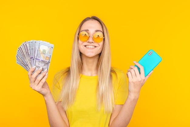 Ritratto di una giovane donna felice che tiene un mazzo di banconote di denaro e mostrando il telefono cellulare su giallo