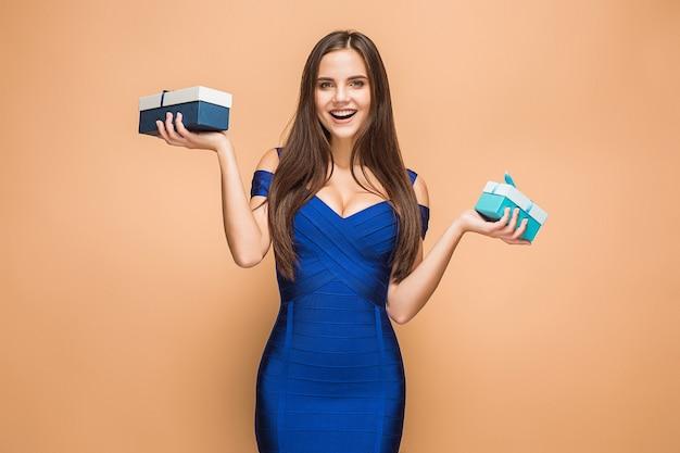 Ritratto di giovane donna felice che tiene un regali su colore marrone