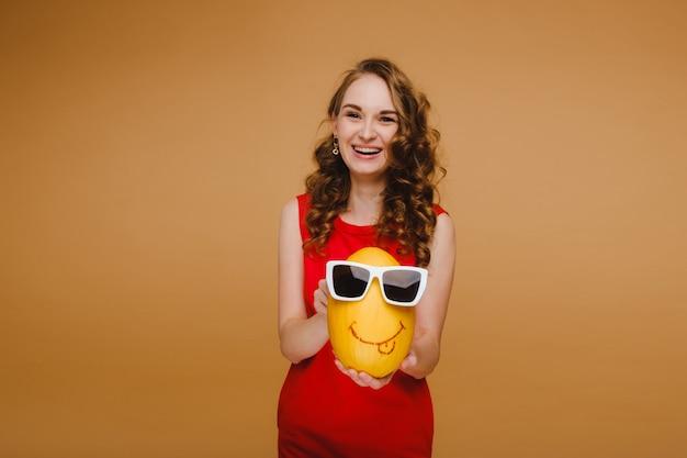 Ritratto di una giovane donna felice che tiene un melone con gli occhiali.