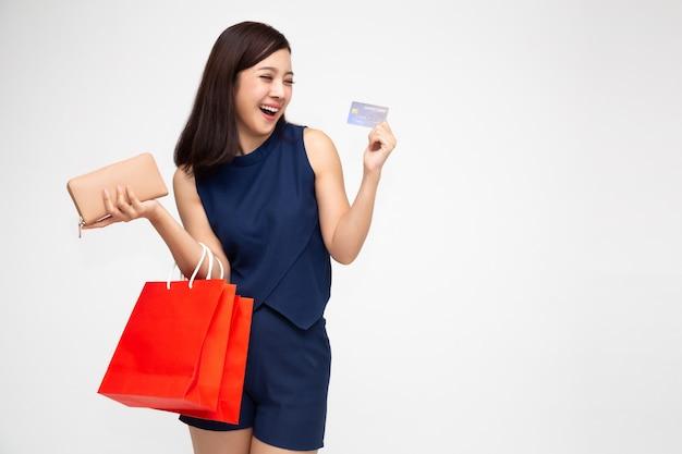 Ritratto di una giovane donna felice che tiene i sacchetti della spesa e carta di credito isolata, vendita di fine anno o liquidazione di promozione di vendita di metà anno per il concetto di shopaholic, modello femminile asiatico