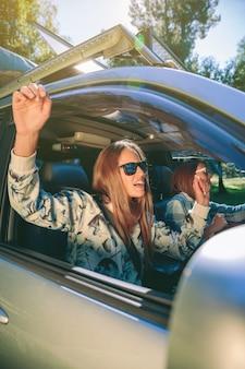 Ritratto di giovane donna felice che alza le braccia e si diverte all'interno dell'auto in un'avventura di viaggio su strada. amicizia femminile e concetto di tempo libero.