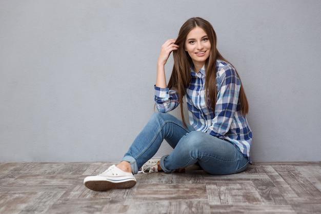 Ritratto di una giovane donna felice seduta sul pavimento su un muro grigio