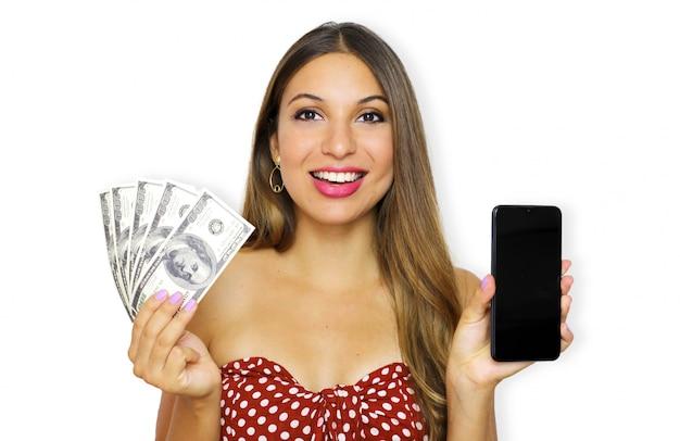 Ritratto di una giovane donna felice che indossa un abito senza spalline che mostra banconote di denaro e smart phone