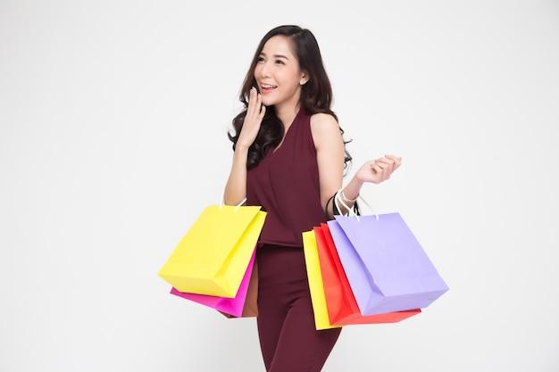 Ritratto delle giovani donne felici in sacchetti della spesa rossi della tenuta del vestito isolati