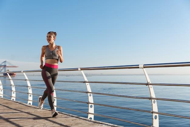 Ritratto di donna sana fitness attraente in esecuzione vicino al mare.