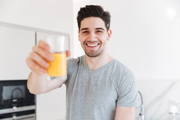 Ritratto dell'uomo in buona salute in abbigliamento casual che sorride e che mostra vetro di succo d'arancia sulla macchina fotografica, mentre facendo colazione in appartamento