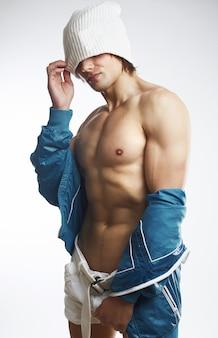 Ritratto di giovane uomo bello muscoloso sano isolato sul muro bianco