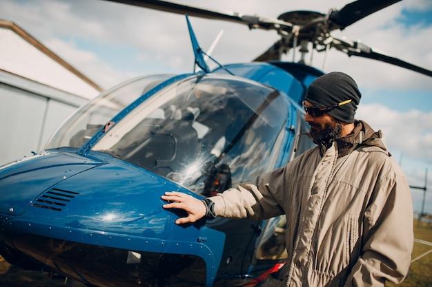 Ritratto di pilota di elicottero in piedi vicino al veicolo nell'aeroporto di campo
