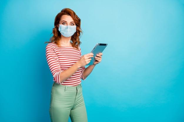 Ritratto di lei attraente ragazza allo zenzero che indossa una maschera di garza di sicurezza utilizzando gadget leggere sfoglia notizie mers cov malattia contaminazione rischio biologico isolato brillante vivido vibrante colore blu