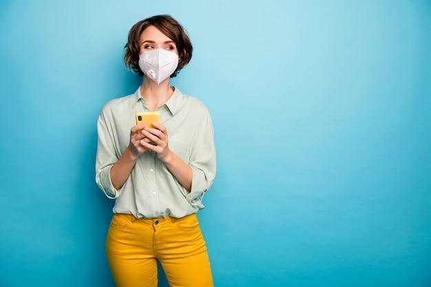 Ritratto di lei ragazza attraente che utilizza gadget indossando maschera di sicurezza anti inquinamento atmosferico problema co2 mers cov prevenzione delle malattie sfoglia notizie isolato sfondo luminoso vivido vibrante colore blu