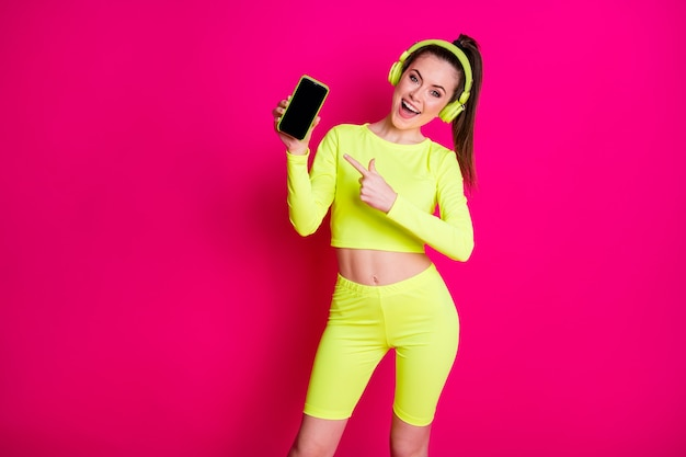 Ritratto di lei attraente bella affascinante ragazza allegra allegra ascolto musica pop dimostrando gadget divertirsi isolato brillante vivido brillantezza vibrante rosa sfondo di colore fucsia