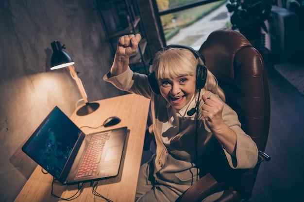 Ritratto di lei bella attraente allegra allegra soddisfatta nonna bionda dai capelli grigi che gioca il campionato di battaglia del concorso di gioco vincere un grande successo al loft industriale moderno interno in stile concreto