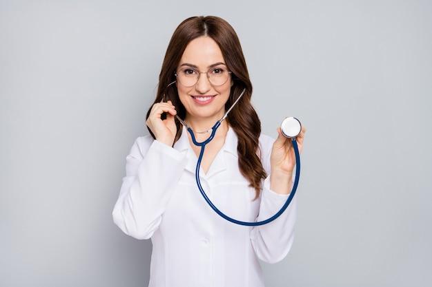 Ritratto di lei bella attraente allegro fiducioso wavyhaired doc esaminando paziente paziente centro diagnostico clinica ascolto battito cardiaco isolato su sfondo grigio colore pastello