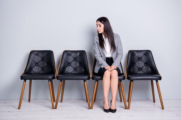 Ritratto di lei bella attraente elegante piuttosto curiosa signora agente broker executive office manager seduto in sedia sbirciando guardando da parte isolato sfondo di colore grigio chiaro pastello