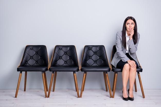 Ritratto di lei bella attraente di classe piuttosto preoccupata frustrata licenziata signora agente broker partner seduto sulla sedia in attesa di un incontro spaventoso isolato sfondo di colore grigio chiaro pastello
