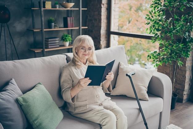 Ritratto di lei bella signora dai capelli grigi calma concentrata attraente che si siede sul divano leggendo una storia d'amore interessante trascorrere del tempo in casa interna in stile moderno loft industriale in mattoni al chiuso