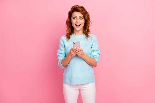 Ritratto di lei bella attraente adorabile affascinante felice stupita allegra allegra ragazza dai capelli ondulati che utilizza la connessione al sito web wireless wi-fi cellulare isolata su sfondo rosa color pastello
