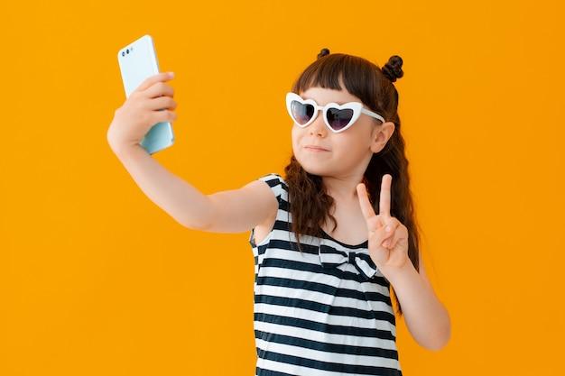 Ritratto di lei bella attraente bella allegra allegra divertente positiva da ragazza pre-adolescente che tiene la cella nelle mani che mostra il segno v facendo selfie post isolato sul muro giallo brillante brillante