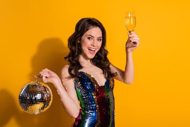 Ritratto di lei bella attraente bella allegra allegra ragazza dai capelli ondulati che beve vino che tiene in mano palla d'argento freddo celibe resto isolato brillante vivido brillantezza vibrante sfondo di colore giallo