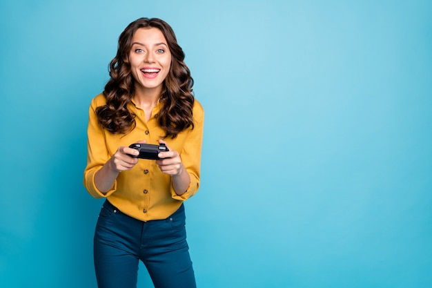 Ritratto di lei bella attraente bella allegra allegra ragazza dai capelli ondulati che gioca video gioco nel fine settimana.