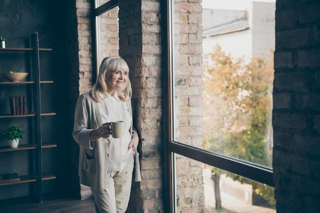 Ritratto di lei bella attraente bella allegra sognante dai capelli grigi bionda nonna di mezza età guardando la finestra che riposa bere cacao al loft industriale in stile moderno interni casa appartamento