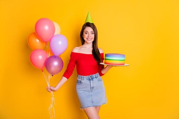 Ritratto di lei bella attraente bella carina allegra allegra funky ragazza che tiene in mano torta fatta in casa palle di elio godendo il tempo libero isolato brillante vivido brillantezza vibrante sfondo di colore giallo