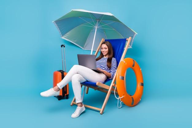 Ritratto di lei bella attraente bella concentrata allegra ragazza seduta su una sedia sotto l'ombrellone utilizzando la programmazione del computer portatile blogging tour esotico isolato brillante vivido brillantezza vibrante sfondo di colore blu