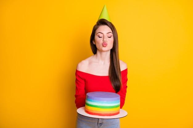 Ritratto di lei bella attraente adorabile adorabile sognante ragazza civettuola che tiene in mano torta fatta in casa a strisce invio bacio dell'aria isolato brillante vivido brillantezza vibrante sfondo di colore giallo