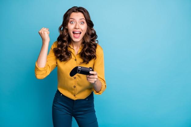 Ritratto di lei bella attraente bella felicissima allegra allegra ragazza dai capelli ondulati che gioca vincitore del videogioco.