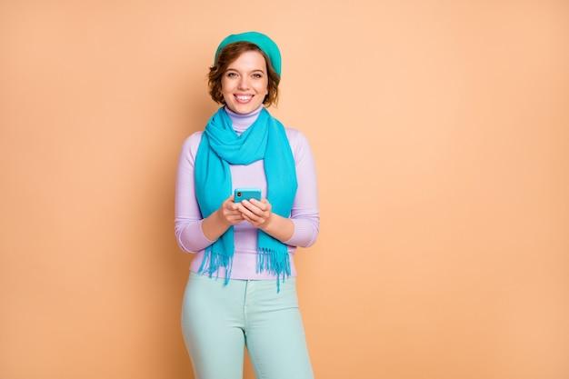 Ritratto di lei bella attraente adorabile piuttosto affascinante allegra ragazza allegra che utilizza il dispositivo che naviga in internet online app 5g isolato su sfondo beige color pastello