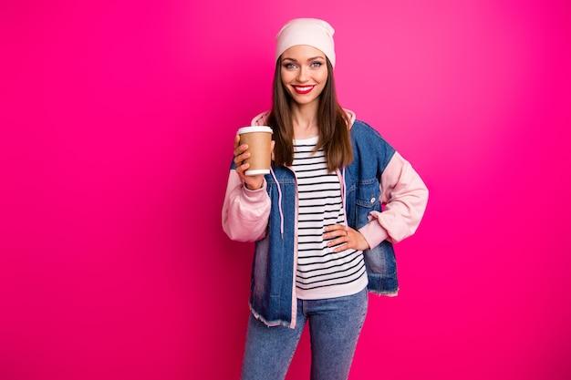 Ritratto di lei bella attraente bella ragazza allegra piuttosto allegra indossando street style tenendo in mano il bicchiere di carta da caffè isolato sopra brillante vivido splendore vibrante colore rosa fucsia