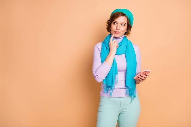 Ritratto di lei bella attraente bella carina ragazza pensierosa di mentalità creativa utilizzando il dispositivo che crea commenti feedback smm isolato sopra priorità bassa di colore pastello beige