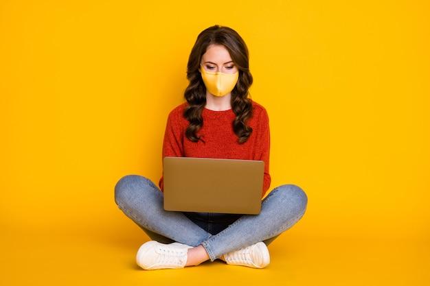Ritratto di lei bella attraente bella ragazza dai capelli ondulati piuttosto concentrata seduta utilizzando laptop e-commerce e-banking quarantena covid isolata su sfondo di colore giallo brillante brillante