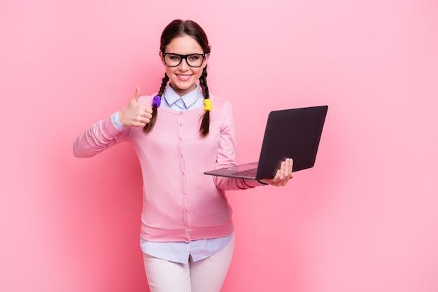 Ritratto di lei bella attraente abbastanza fiduciosa allegra ragazza dai capelli castani che tiene in mano il computer portatile che mostra il servizio di consulenza pubblicitaria thumbup isolato su sfondo rosa color pastello