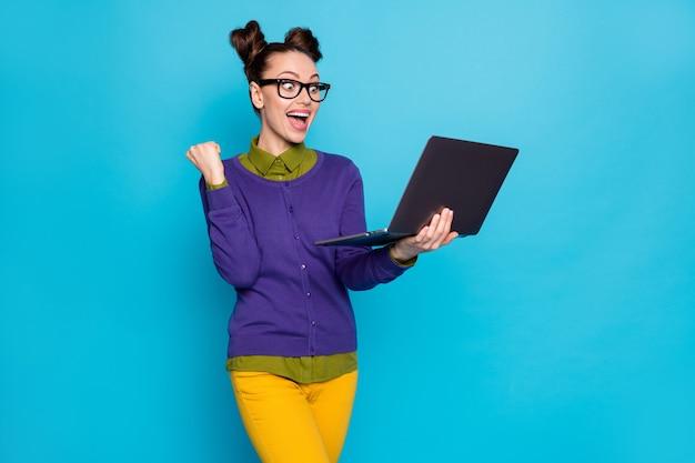 Ritratto di lei bella attraente intelligente intelligente ragazza allegra che tiene in mano il computer portatile celebrando vincere vincitore isolato brillante vivido brillare vibrante blu verde acqua turchese colore sfondo