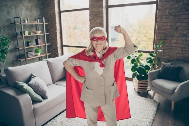 Ritratto di lei bella attraente forte potente allegro allegro contento pronto nonna dai capelli grigi che indossa il costume rosso che mostra i muscoli bicipiti tricipiti industriale mattone loft stile moderno interni