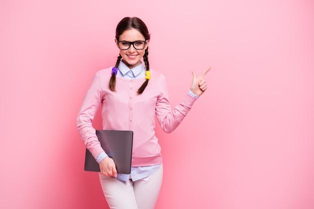 Ritratto di lei bella allegra fiduciosa adolescente dai capelli castani che tiene in mano il computer portatile che mostra copia spazio annuncio consigli studio imparare consigliare sfondo rosa pastello colore isolato